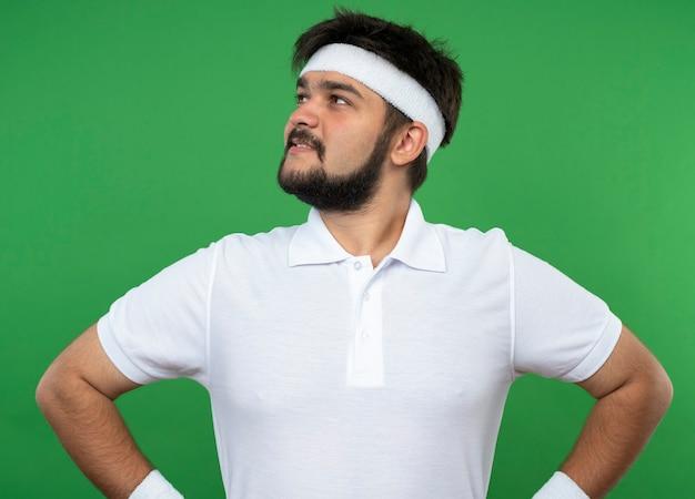 Heureux jeune homme sportif regardant côté portant un bandeau et un bracelet mettant les mains sur la hanche isolé sur vert