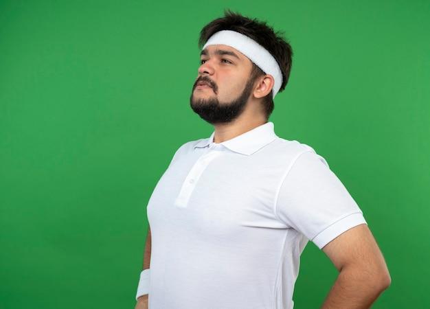 Heureux jeune homme sportif regardant côté portant un bandeau et un bracelet mettant les mains sur la hanche
