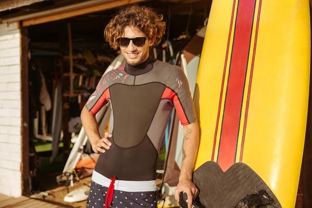 Heureux jeune homme surfer à lunettes de soleil debout sur la plage