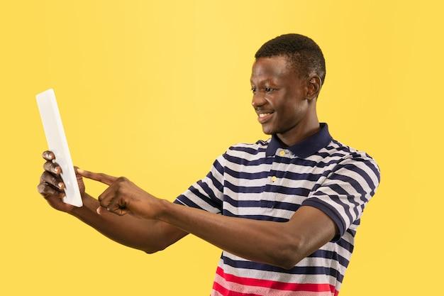 Heureux jeune homme avec tablette isolée sur le mur jaune du studio