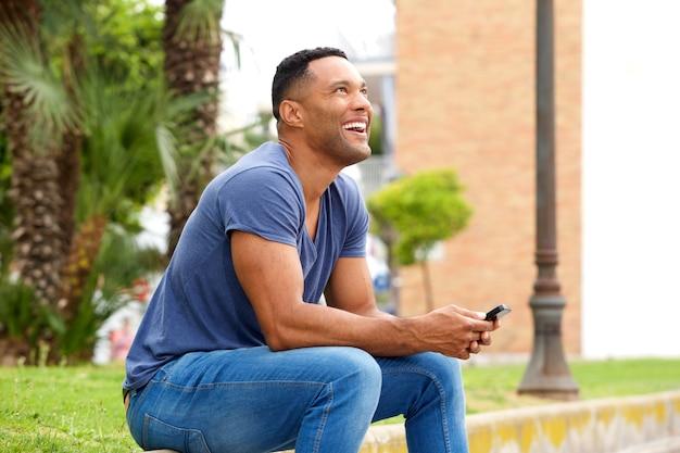 Heureux jeune homme avec un téléphone portable assis sur le trottoir et en détournant les yeux