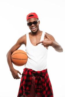 Heureux jeune homme tenant un ballon de basket et pointant loin