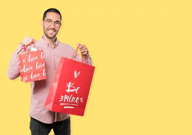 Heureux jeune homme tenant un gros coeur de jouet et faisant des gestes à propos de la saint-valentin