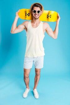 Heureux jeune homme tenant une planche à roulettes jaune
