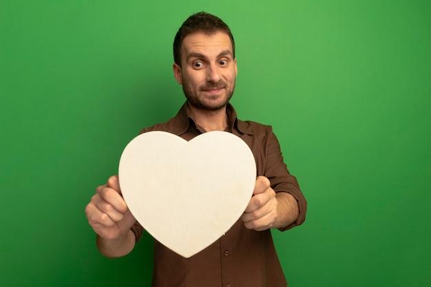 Heureux jeune homme tenant et regardant en forme de coeur isolé sur mur vert