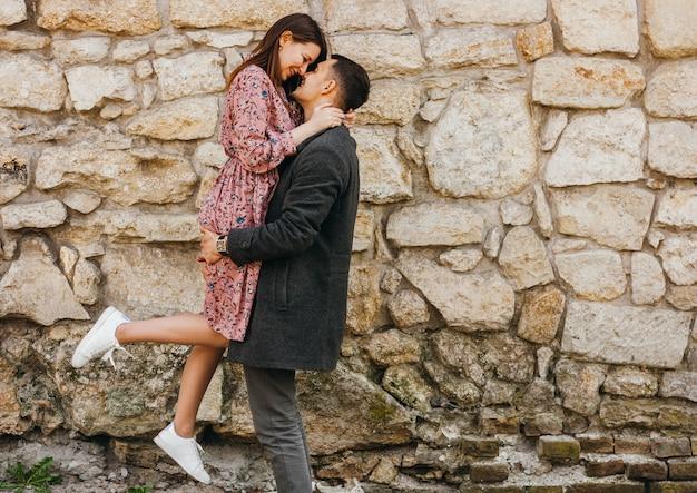 Heureux jeune homme tenant sa femme dans ses bras contre le mur de pierre.