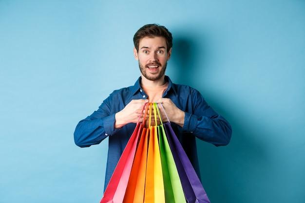 Heureux jeune homme tenant des sacs colorés et souriant excité, acheter des cadeaux, debout sur fond bleu.