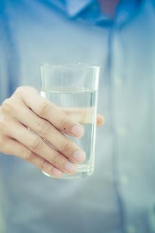 Heureux jeune homme tenant un verre d'eau à la main. concept de soins de santé.