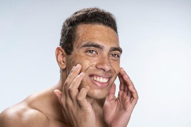 Heureux jeune homme touchant son visage avec un masque anti-humidité