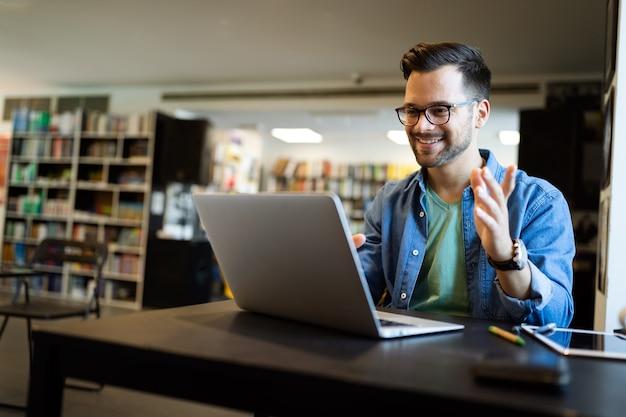 Heureux jeune homme travaillant sur ordinateur portable. les gens de la technologie travaillent concept d'étude
