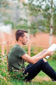 Heureux jeune homme urbain avec livre en plein air