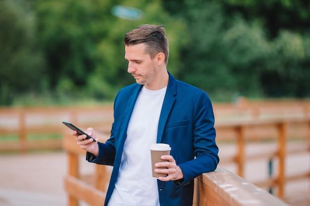 Heureux jeune homme urbain travaillant et buvant du café en plein air de la ville européenne