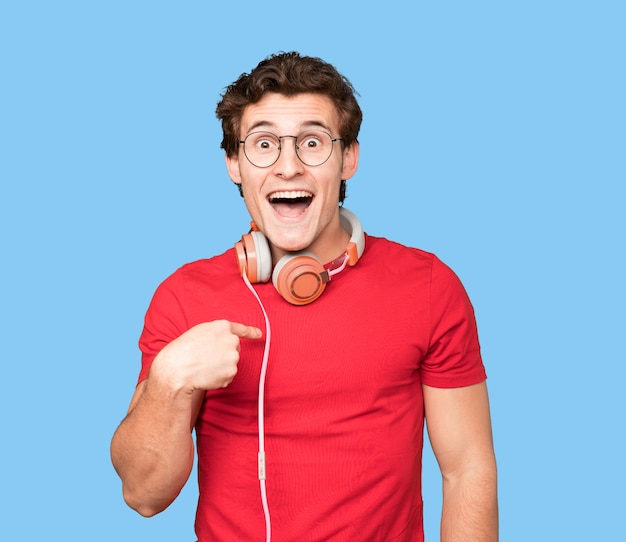 Heureux jeune homme utilisant des écouteurs et un smartphone et pointant vers lui-même avec son doigt