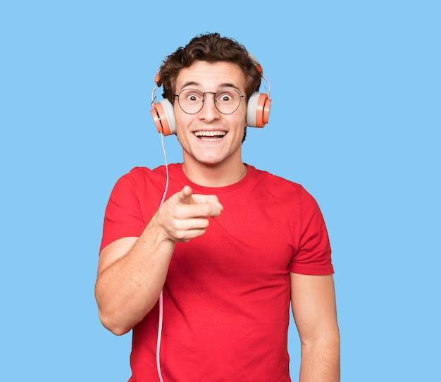 Heureux jeune homme utilisant des écouteurs et un smartphone et pointant vers vous