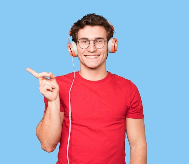 Heureux jeune homme utilisant des écouteurs et un smartphone et pointant
