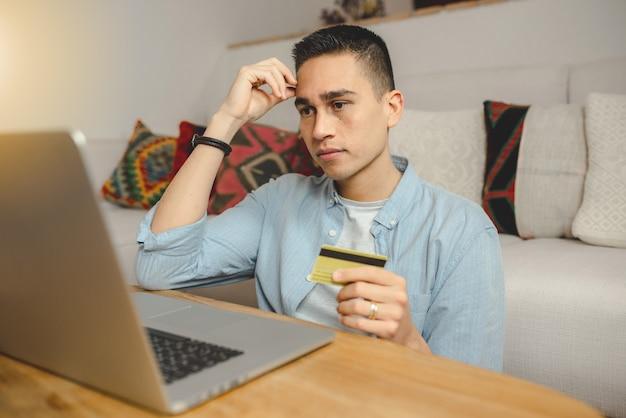 Heureux jeune homme utilisant un ordinateur portable pour faire des achats en ligne.
