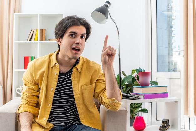Heureux jeune homme en vêtements décontractés surpris montrant l'index ayant une nouvelle idée assis sur la chaise dans un salon lumineux
