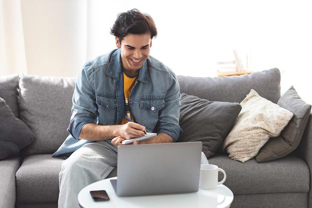 Heureux jeune indépendant caucasien réussi assis sur le canapé au bureau à domicile avec un ordinateur portable dans des vêtements décontractés parle par vidéoconférence