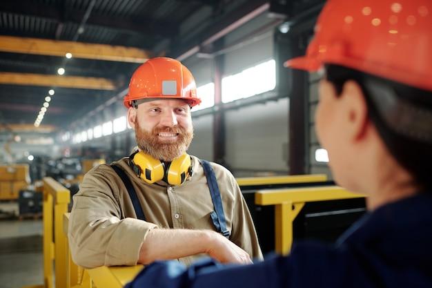 Heureux jeune ingénieur barbu en casque debout devant son collègue lors de la discussion des points de travail