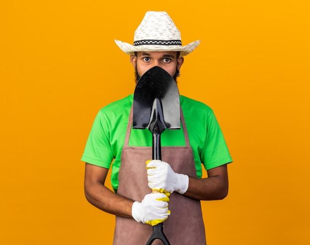 Heureux jeune jardinier afro-américain portant un chapeau de jardinage et des gants recouverts d'un visage isolé sur un mur orange