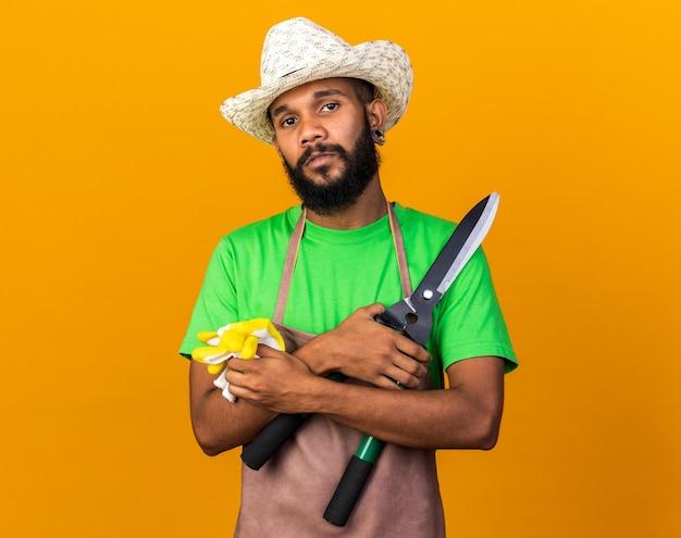 Heureux jeune jardinier afro-américain portant un chapeau de jardinage tenant des tondeuses avec des gants