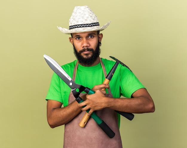 Heureux jeune jardinier afro-américain portant un chapeau de jardinage tenant et traversant des tondeuses avec un râteau isolé sur un mur vert olive