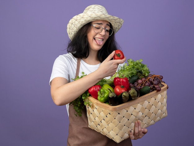 Heureux jeune jardinier femme brune à lunettes optiques et en uniforme portant chapeau de jardinage sort la langue et détient un panier de légumes à la tomate sur le mur violet