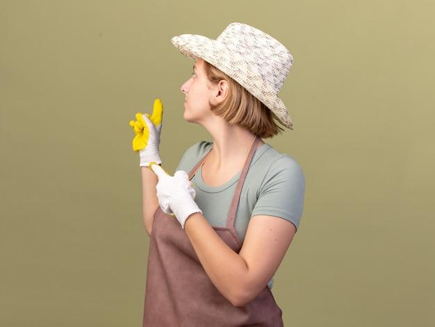 Heureux jeune jardinier femme slave portant chapeau de jardinage et des gants à la recherche et pointant vers l'arrière sur vert olive