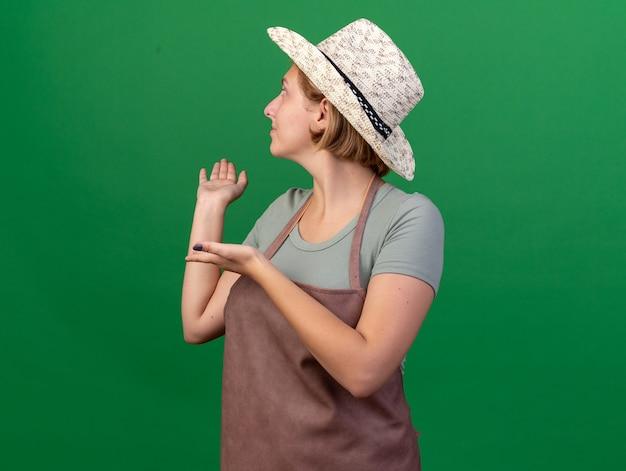 Heureux jeune jardinier femme slave portant chapeau de jardinage à la recherche et pointant vers l'arrière sur le vert