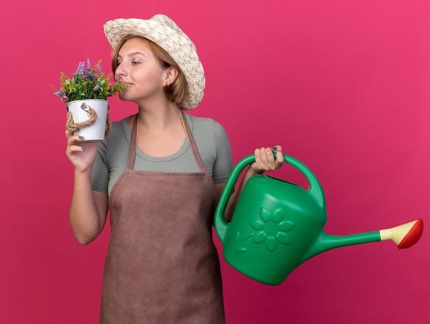 Heureux jeune jardinier femme slave portant chapeau de jardinage tenant un arrosoir et reniflant des fleurs en pot de fleurs sur rose