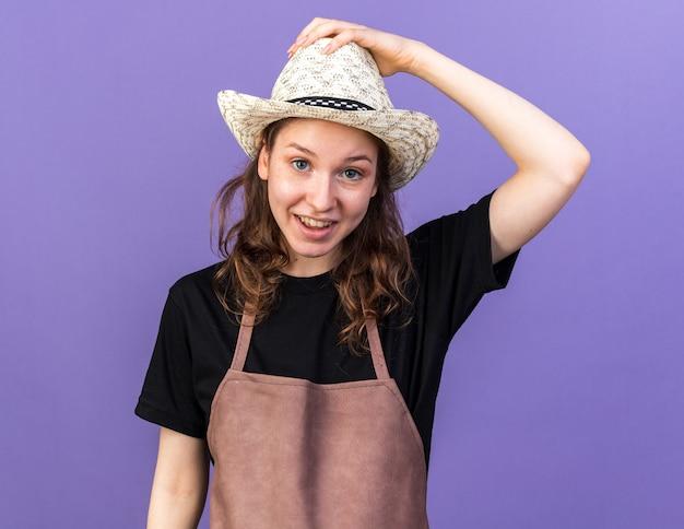 Heureux jeune jardinière portant chapeau de jardinage holding hat