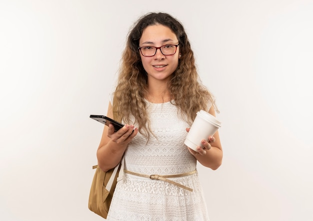 Heureux jeune jolie écolière portant des lunettes et sac à dos tenant une tasse de café et un téléphone mobile isolé sur un mur blanc