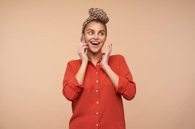 Heureux jeune jolie femme aux cheveux bruns avec maquillage naturel souriant joyeusement tout en ayant une conversation téléphonique agréable, isolée sur un mur beige