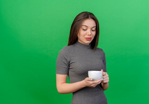 Heureux jeune jolie femme tenant et regardant la tasse isolée sur fond vert avec espace copie