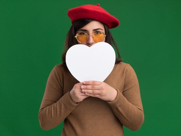 Heureux jeune jolie fille caucasienne avec béret chapeau dans des lunettes de soleil tenant en forme de coeur devant le visage sur le vert