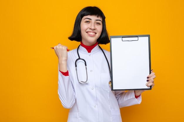 Heureux jeune jolie fille caucasienne en uniforme de médecin avec stéthoscope tenant un stylo et un presse-papiers