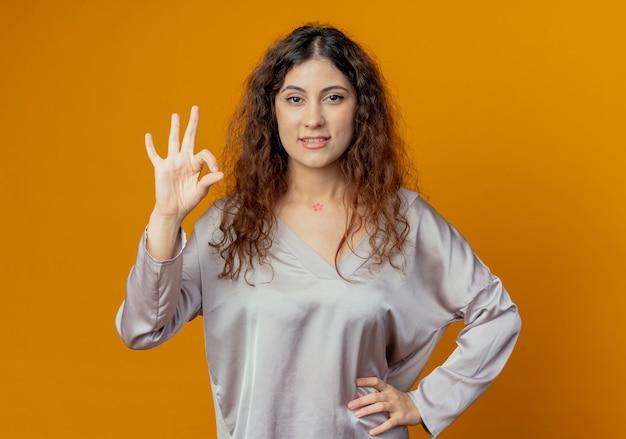 Heureux jeune jolie fille montrant le geste okey et mettant la main sur la hanche isolé sur mur jaune