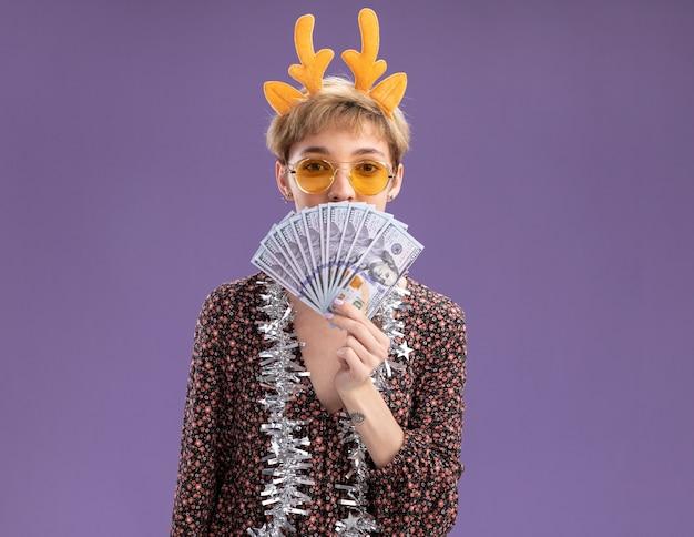 Heureux jeune jolie fille portant bandeau de bois de renne et guirlande de guirlandes autour du cou avec des lunettes tenant de l'argent regardant la caméra par derrière isolé sur fond violet avec espace de copie