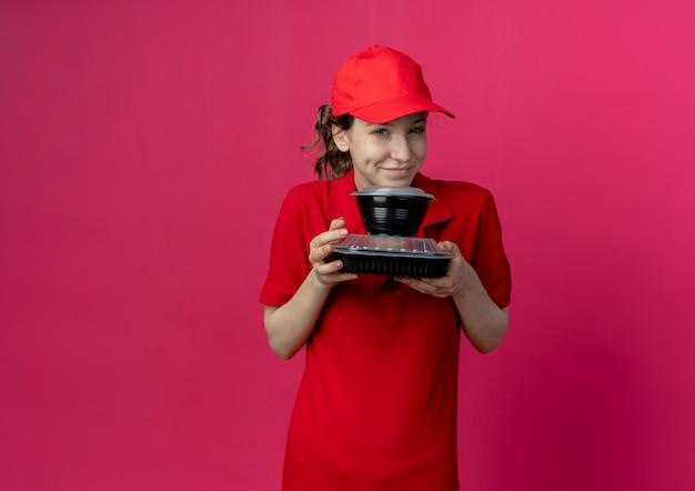 Heureux jeune jolie livreuse portant un uniforme rouge et une casquette tenant des contenants de nourriture isolés sur fond cramoisi avec espace de copie