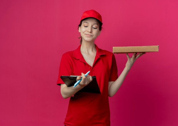 Heureux jeune jolie livreuse en uniforme rouge et cap tenant le presse-papiers et stylo avec paquet de pizza regardant le presse-papiers isolé sur fond cramoisi avec espace de copie