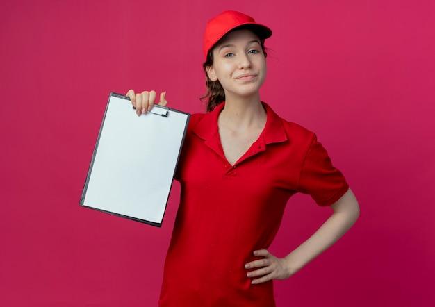 Heureux jeune jolie livreuse en uniforme rouge et casquette montrant le presse-papiers et mettant la main sur la taille isolé sur fond cramoisi