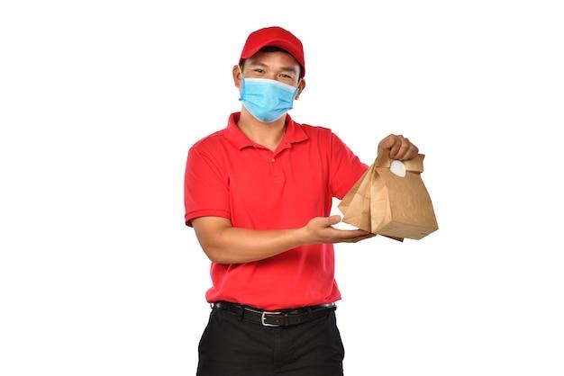 Heureux jeune livreur asiatique en uniforme rouge, masque médical porter des sacs de nourriture et de boisson dans les mains isolés sur fond blanc