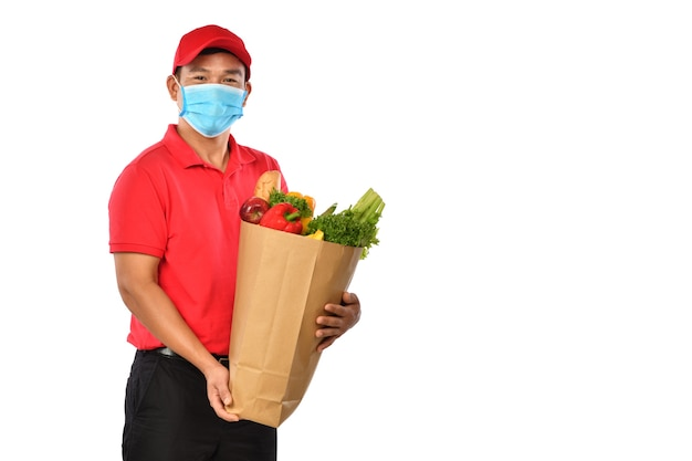 Heureux jeune livreur asiatique en uniforme rouge, masque médical transporter le sac d'épicerie dans les mains isolé sur fond blanc