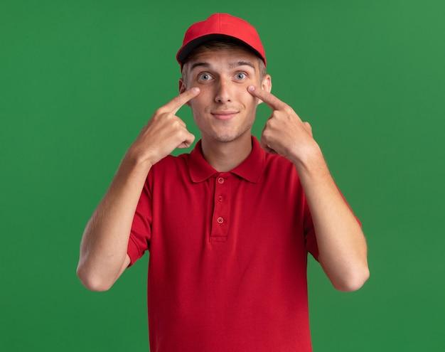 Heureux jeune livreur blond met les doigts sur les paupières isolées sur un mur vert avec espace de copie