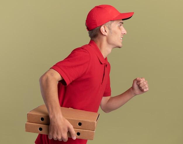 Heureux jeune livreur blonde se tient sur le côté tenant des boîtes de pizza faisant semblant de fonctionner sur vert olive