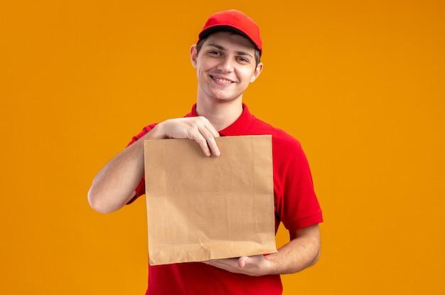 Heureux jeune livreur caucasien en chemise rouge tenant un emballage alimentaire