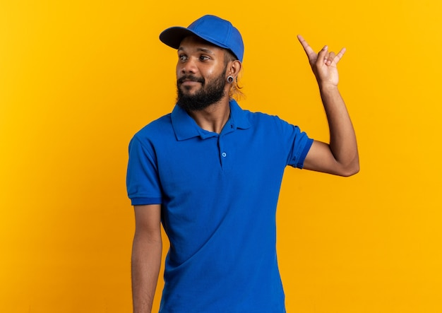 Heureux jeune livreur gesticulant des cornes et regardant le côté isolé sur un mur orange avec espace pour copie