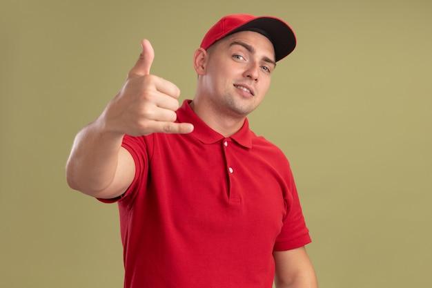 Heureux jeune livreur en uniforme et casquette montrant un geste d'appel téléphonique isolé sur un mur vert olive