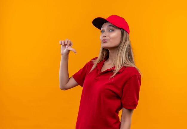 Heureux jeune livreuse portant l'uniforme rouge et une casquette se pointe vers elle-même