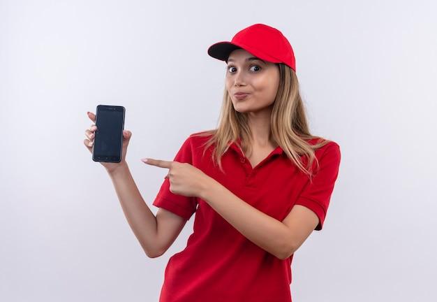 Heureux jeune livreuse portant un uniforme rouge et une casquette tenant et pointe vers le téléphone isolé sur un mur blanc